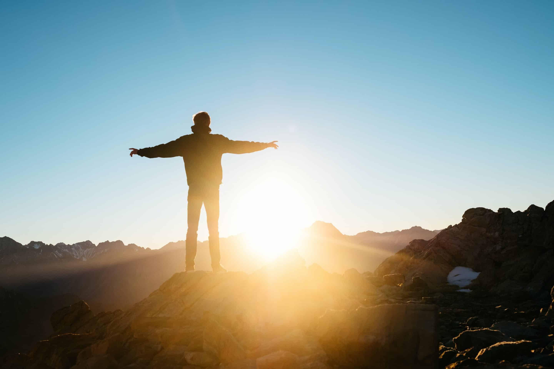 Homme avec les bras écarté face au soleil lumineux et sentiment de liberté suite au traitement des céphalées de tension