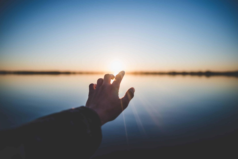 personne qui tend la main vers le soleil pour retrouver espoir dans la guérison de ses céphalées de tension chroniques quotidiens