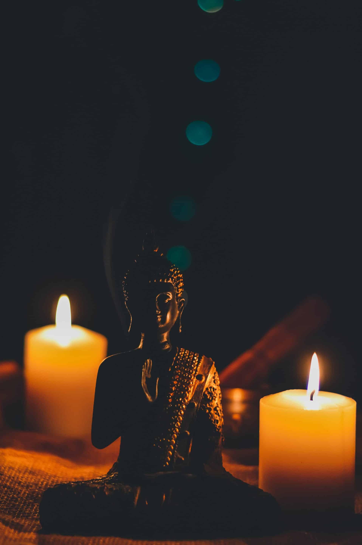 Bouddha entouré de deux bougies dans le noir