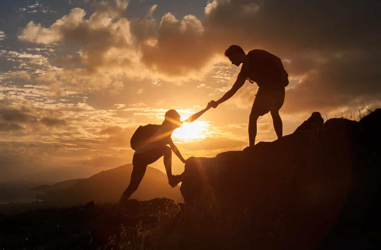 Une personne aide une autre à gravir une montagne